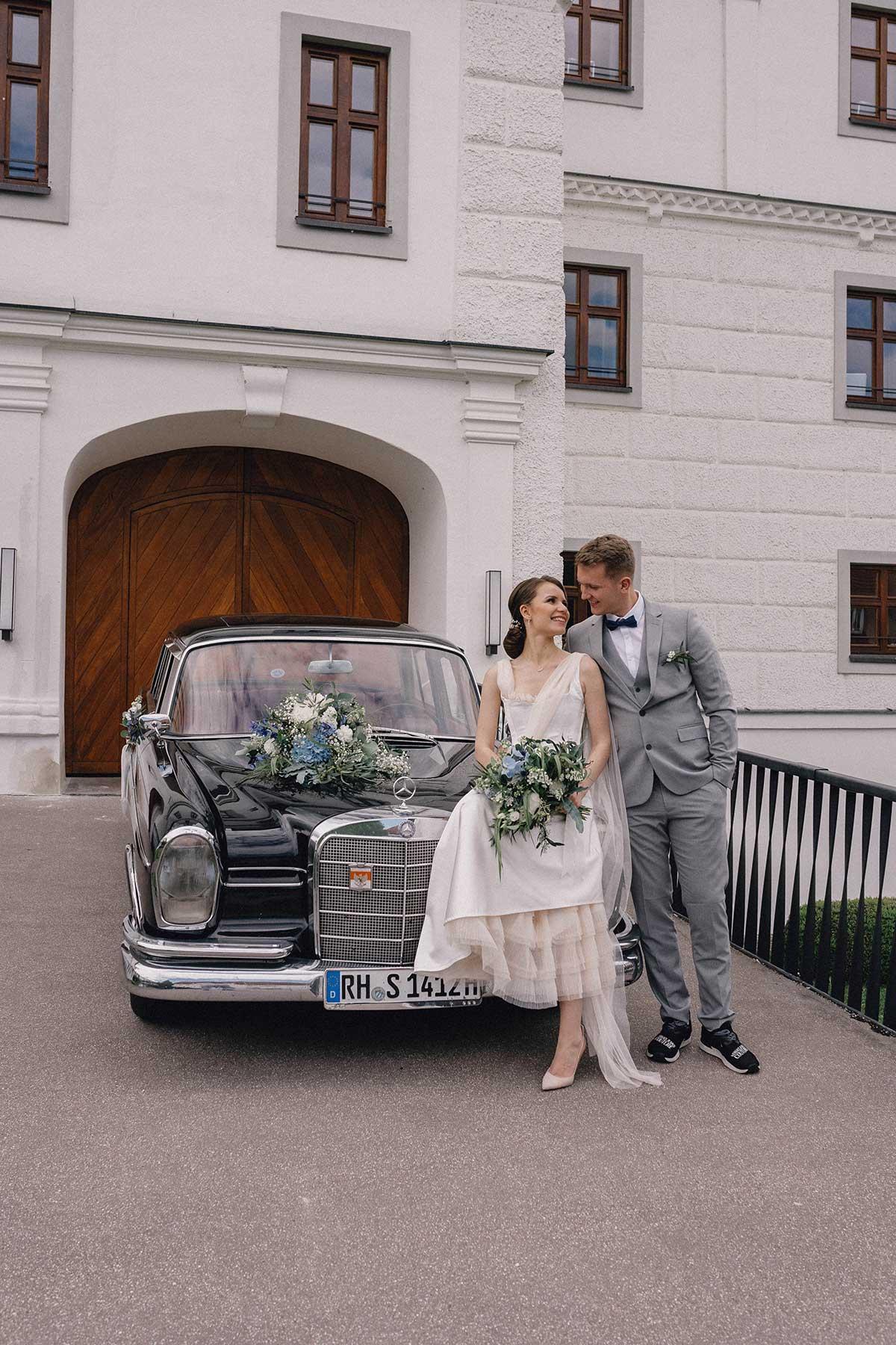 Braut und Bräutigam stehen vor einem Auto
