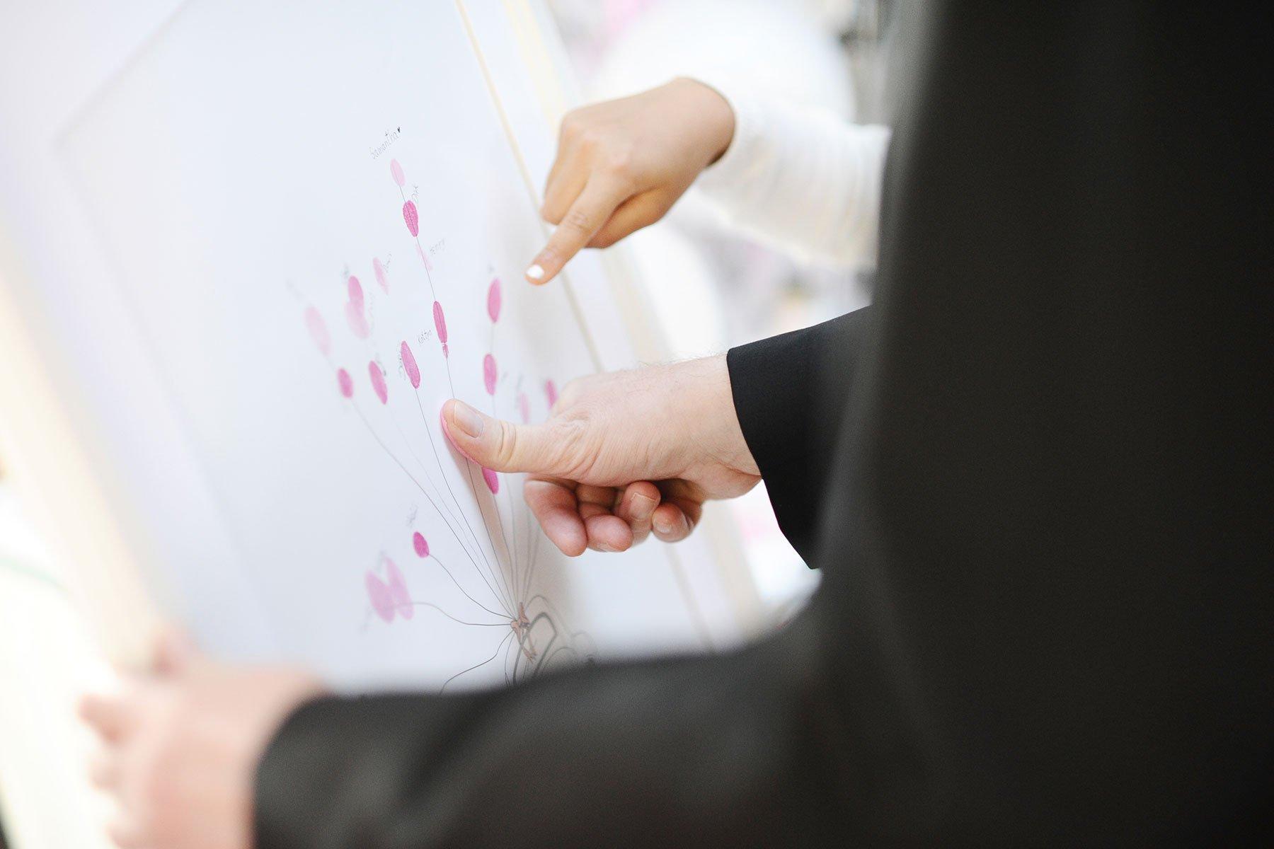 Kind zeigt Hochzeitsgast wie das Fingerabdruck-Bild funktioniert