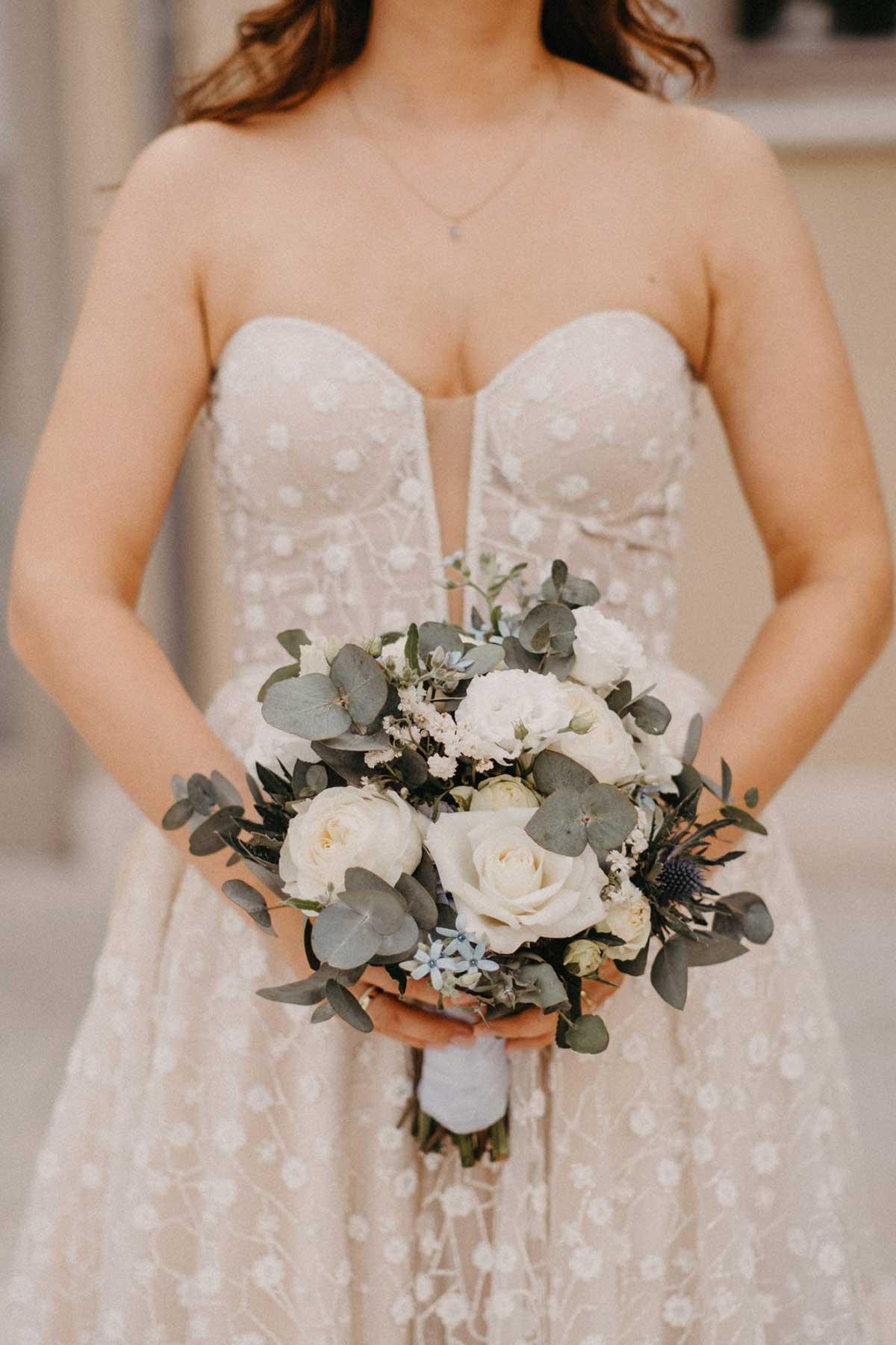 Braut hält Brautstrauß mit Blumen in Weiß und Pastell Blau