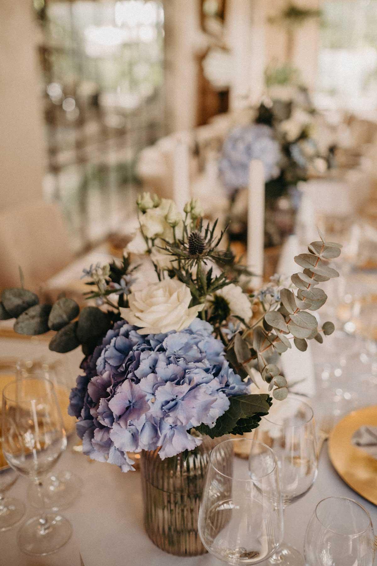 Tischdeko mit Blumen in Braut hält Brautstrauß mit Blumen in Weiß und Pastell Blau