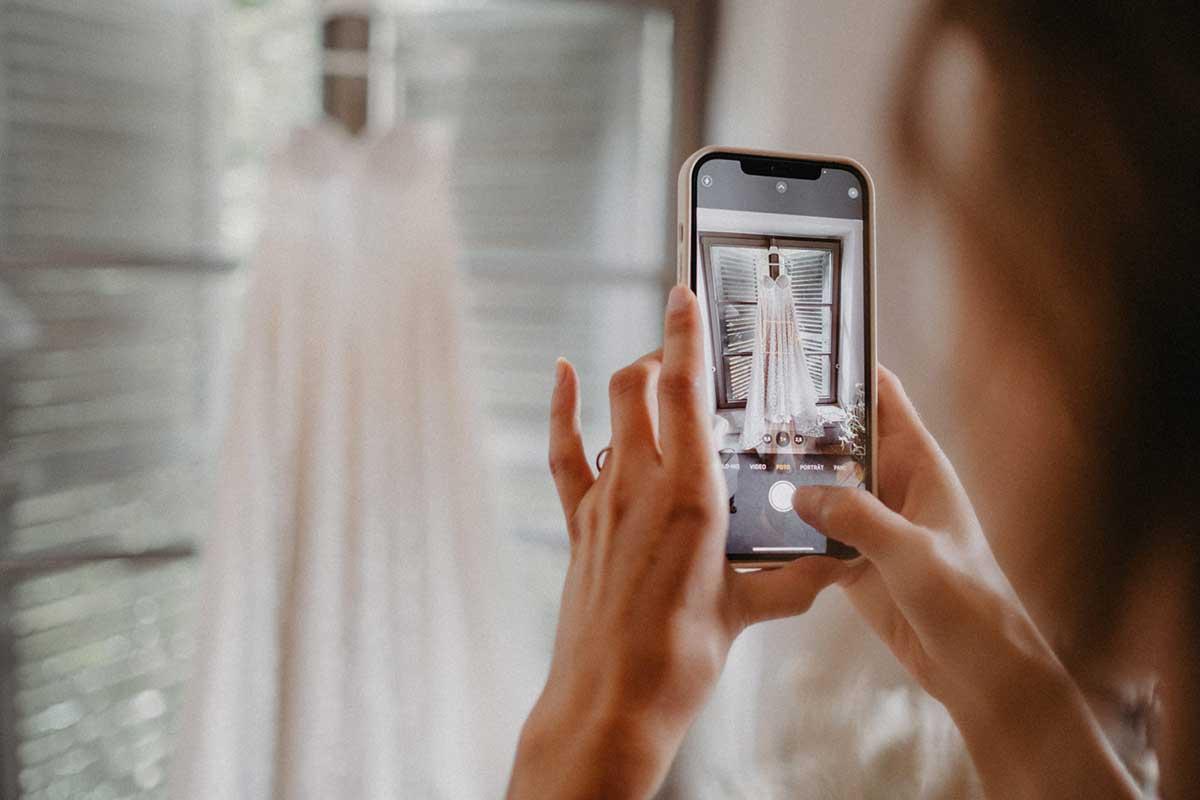 Person macht Foto vom Brautkleid mit Smartphone