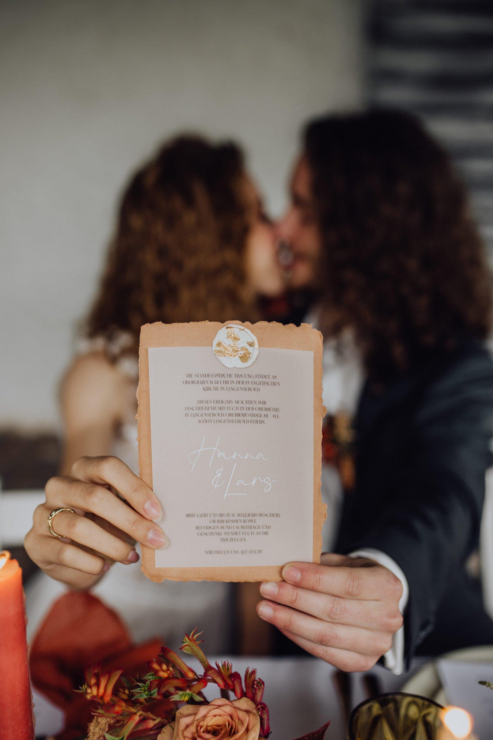 Braut und Bräutigam halten Einladungskarte zur Hochzeit