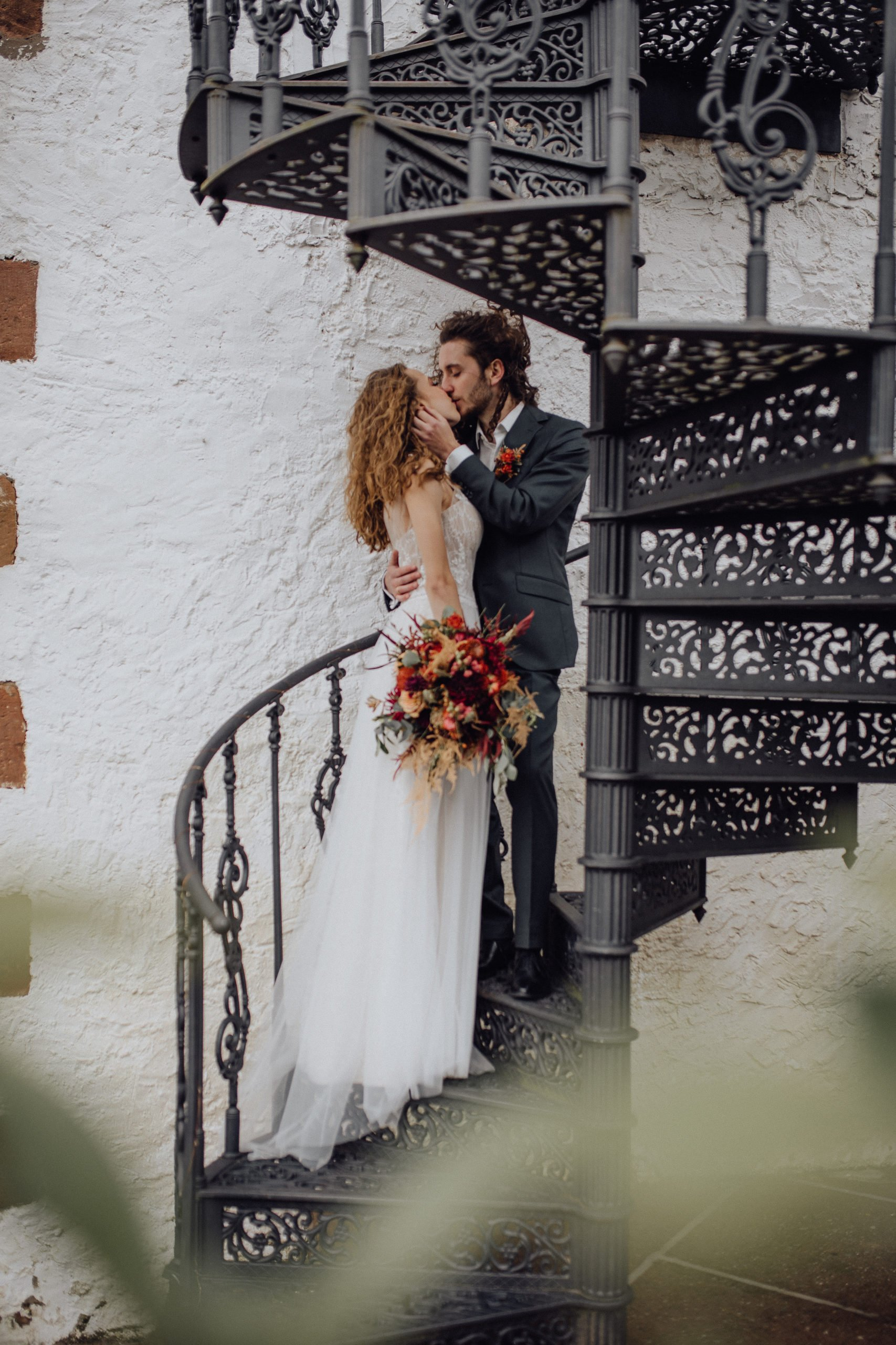 Braut und Bräutigam stehen auf einer Treppe und küssen sich